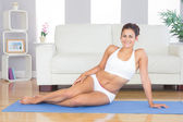 Young sporty woman posing sitting on an exercise mat — Stock fotografie
