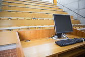 Computer monitor with empty seats in a lecture hall — Stock Photo