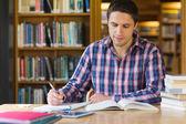 Mannelijke student schrijven van notities op bureau in de bibliotheek — Stockfoto