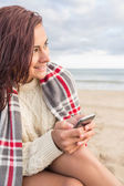 Woman covered in blanket with cellphone at beach — Stock Photo