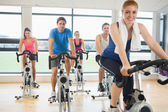 Happy woman teaches spinning class to four people — Photo