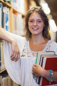 Kütüphanede duran gülümseyen kız öğrenci — Stok fotoğraf