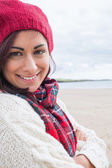 Woman in knitted hat and pullover smiling at beach — Stock Photo