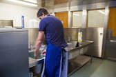 Kitchen porter washing up at sink — Stock Photo