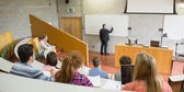 Male teacher with students at the lecture hall — Stock Photo