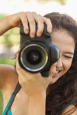 Smiling young woman taking a picture — Stock Photo