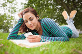 Cheerful casual student lying on grass listening to music — Stock Photo