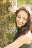 Casual smiling brunette embracing a tree with closed eyes — Stock Photo