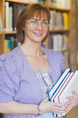 Female librarian posing holding some books — Stock Photo