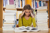 Frustrated pretty student studying between piles of books — Stockfoto