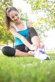 Happy active brunette tying her shoelaces — Stock Photo