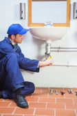 Concentrating plumber repairing sink — Stock Photo