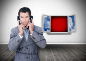 Angry businessman wrapped in cables phoning — Stockfoto