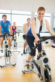 Happy woman teaches spinning class to four people — Stockfoto