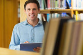 Smiling mature student with tablet PC in library — Stock Photo
