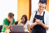 σερβιτόρα γράφοντας μια τάξη με τους μαθητές χρησιμοποιώντας φορητό υπολογιστή στο καφέ — Φωτογραφία Αρχείου