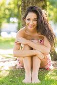 Stylish smiling brunette sitting under a tree — Stock Photo