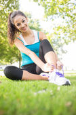 Cheerful active brunette tying her shoelaces — Stock Photo