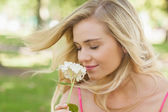 Gorgeous content woman smelling a flower with closed eyes — Stock Photo