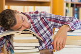 Tired handsome student resting head on piles of books — Stock Photo