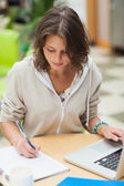 Concentrated female student doing homework by laptop — Stock Photo