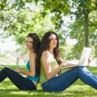 Two cute brunette women sitting on a lawn smiling at camera — Stock Photo