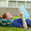 Stock Photo: Gorgeous concentrating student lying on grass reading notes