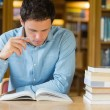 Serious mature student studying at library desk — Stock Photo #36190525