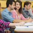 Smiling female with other students writing notes at lecture hall — Stock Photo