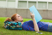 Gorgeous concentrating student lying on grass reading notes — Stock Photo