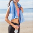 Beautiful smiling healthy woman with water bottle on beach — Stock Photo #36242787