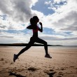 Full length of silhouette healthy woman jogging on beach — Stock Photo
