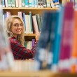Smiling female student reading book in the library — Stock Photo #36243029