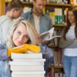 Female student with stack of books while others in background at library — Stock Photo #36243163