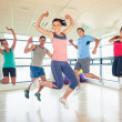Fitness class and instructor jumping in fitness studio — Stock Photo