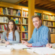 Group of students writing notes at library desk — Stock Photo #36244023