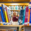 Smiling female student reading book in the library — Stock Photo #36244027
