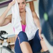 Stockfoto: Tired young womworking out on row machine