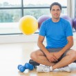 Young man sitting with dumbbells in fitness studio — Stock Photo