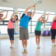 Fitness class and instructor standing in Namaste position — Stock Photo #36244555