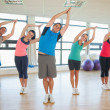 Stock Photo: Fitness class and instructor standing in Namaste position