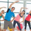 Stock Photo: Smiling people doing power fitness exercise at yogclass