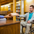 Student in wheelchair at the library counter — Stock Photo