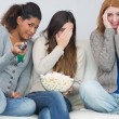 Scared friends with remote control and popcorn bowl on sofa — Stockfoto