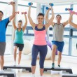 Instructor with fitness class performing step aerobics exercise with dumbbells — Stock Photo #36244699