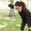 Tired woman taking a break while jogging in park — Stock Photo #36244795