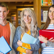 Students with folders standing against bookshelf in library — Stock Photo #36245173