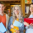 Students with folders standing against bookshelf in library — Stock Photo