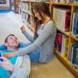 Romantic couple with books at the library aisle — Stock Photo #36245227