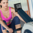 Stockfoto: Womworking out on row machine in fitness studio